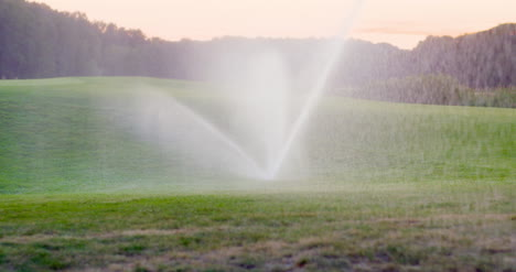 Medium-Shot-Of-Grass-Sprinkler-Splashes-Water-Over-The-Lawn