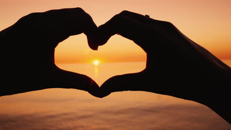 Woman-Shows-Her-Heart-Shape-On-The-Background-Of-The-Sea-Where-The-Sun-Goes-Down