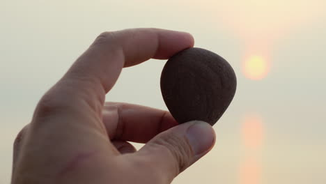 Hand-Holds-Pebbles-On-A-Background-Of-Sea-And-Sun