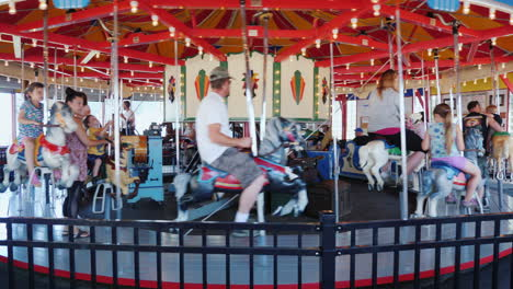Children-With-Parents-Ride-On-An-Old-Carousel-At-The-Fair