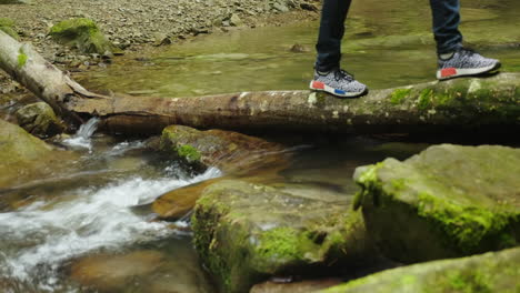 Cross-The-Mountain-Stream-Over-A-Fallen-Tree-A-Person-Crosses-An-Obstacle-Only-Foots-In-Shoes-Are-Vi