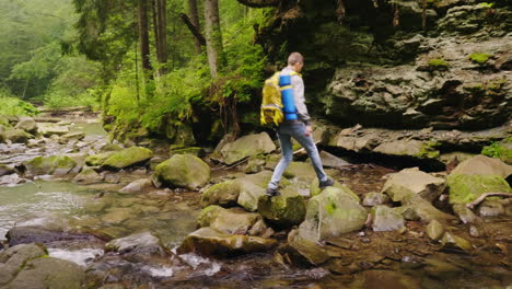 A-Young-Male-Tourist-Crosses-A-Mountain-River-In-The-Forest-4K-Video