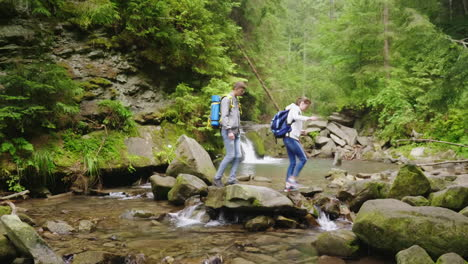 A-Young-Couple-Of-Tourists-With-Backpacks-Crosses-A-Mountain-River-In-The-Forest-Hd-Video