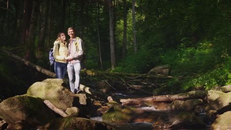A-Young-Couple-Of-Tourists-Admire-The-Forest-Landscape-Stand-On-A-Large-Rock-Near-A-Mountain-River-O