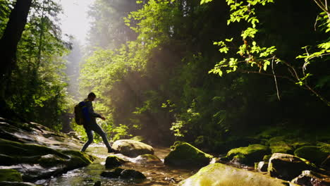 Silhouette-Of-A-Man-With-A-Backpack-Crosses-A-Mountain-River-Or-Stream-Beautiful-Forest-With-Rays-Of