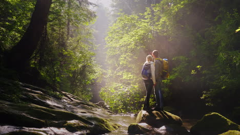 A-Pair-Of-Travelers-Are-Photographed-In-A-Picturesque-Place-In-A-Forest-Near-A-Mountain-River-4K-Vid