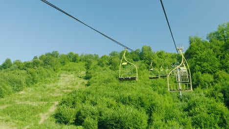 Seats-Of-The-Ski-Lift-They-Move-Upwards-Against-The-Background-Of-A-Forest-Covered-With-A-Forest-Hol