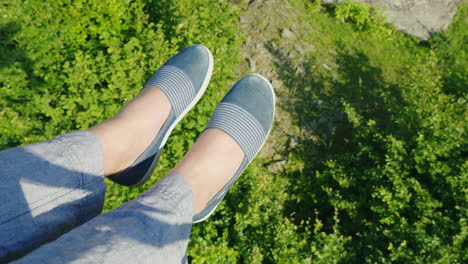 Female-Feet-Are-Flying-Over-The-Precipice-Covered-With-Forest-Going-On-The-Ski-Lift-In-The-Frame-You