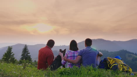 A-Couple-Of-Tourists-With-A-Dog-Admire-The-Beautiful-Scenery-In-The-Mountains-They-Sit-On-The-Ground