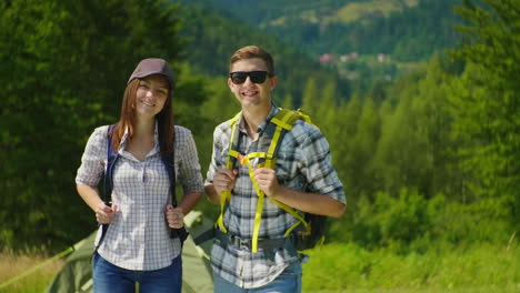 Portrait-Of-A-Couple-Of-Happy-Tourists-With-Backpacks-Smile-Look-At-The-Camera-4K-Video