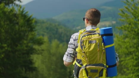 A-Tourist-Man-With-A-Yellow-Backpack-Looks-Forward-To-A-Beautiful-Mountain-Landscape-With-A-Forest-I