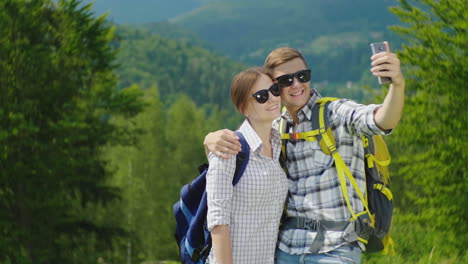 A-Young-Couple-Of-Tourists-With-Backpacks-Take-Pictures-Of-Themselves-With-A-Smartphone-On-A-Beautif