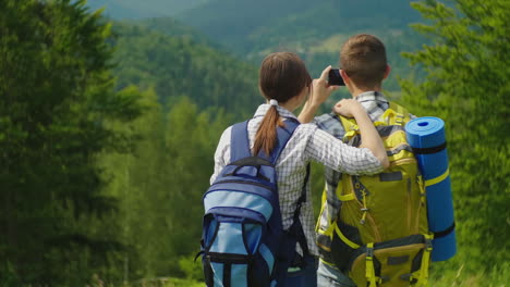 A-Couple-Of-Travelers-With-Backpacks-Take-Pictures-Of-A-Beautiful-Mountain-Landscape-Active-Vacation