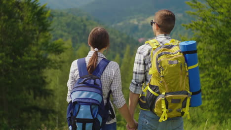 A-Couple-Of-Tourists-With-Backpacks-Enter-The-Frame-Enjoy-The-Beautiful-Mountain-Scenery-Clear-Summe