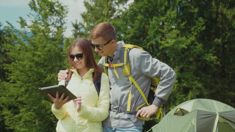 A-Young-Couple-Of-Tourists-Enjoy-A-Tablet-In-The-Camping-Stand-Near-The-Tent-Technology-On-Vacation-