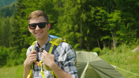 A-Young-Man-With-A-Backpack-Is-Looking-At-The-Camera-Standing-In-The-Background-Of-A-Camping-Tent-Po