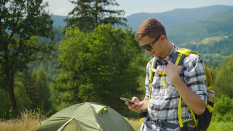 A-Young-Man-With-A-Backpack-Use-A-Smartphone-In-The-Camping-Always-In-Touch-App-For-Tourism