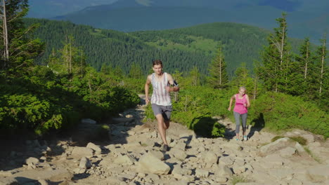 Extreme-Running-A-Woman-With-A-Personal-Trainer-Runs-Down-A-Steep-Mountain-Path-In-The-Mountains-Fro