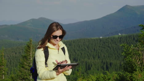 A-Female-Tourist-In-A-Yellow-Jacket-Uses-A-Tablet-It-Stands-Against-The-Background-Of-The-Mountains-