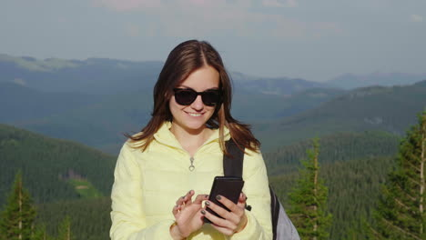 Young-Woman-Enjoying-A-Smartphone-On-A-Picturesque-Backdrop-Of-Mountains-Covered-With-Forest-Always-