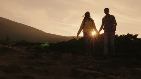 A-Young-Couple-Of-Tourists-With-Backpacks-Walking-Along-A-Mountain-Trail-In-The-Rays-Of-The-Setting-