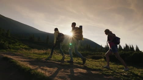 A-Group-Of-Friends-With-Backpacks-Rises-Up-The-Mountain-In-The-Rays-Of-The-Setting-Sun-Active-Lifest