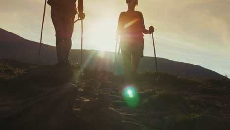 Dawn-Of-The-Sun-In-The-Mountains-Silhouettes-Of-Two-Travelers-Meet-Descend-Along-A-Mountain-Path-4K-