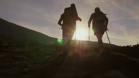 Silhouettes-A-Pair-Of-Tourists-Climbing-A-Mountain-In-The-Rays-Of-The-Setting-Sun-Back-View-Concept-