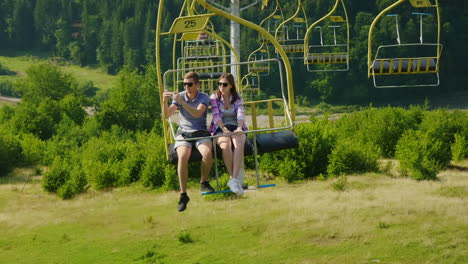 A-Happy-Young-Couple-Is-Riding-On-A-Ski-Lift-Photograph-Landscapes-Holidays-In-The-Mountains-In-Summ
