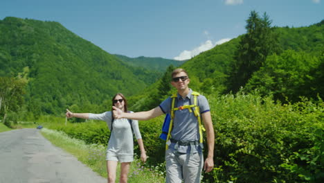 A-Young-Couple-Of-Tourists-With-Backpacks-Are-Voting-On-The-Road---They-Stop-Passing-Cars-Hold-Your-