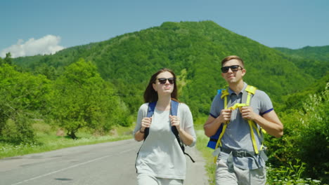 A-Young-Tourist-Couple-Walks-Along-The-Road-To-Beautiful-Mountains-Covered-With-Forest-Active-Way-Of