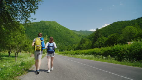 A-Couple-Of-Tourists-With-Backpacks-Are-Walking-Along-The-Asphalt-Road-Towards-The-Beautiful-Green-M