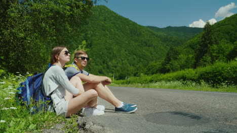 A-Couple-Of-Tired-Tourists-With-Backpacks-Rest-On-The-Roadside-In-A-Picturesque-Place-In-The-Backgro