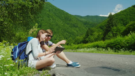 A-Pair-Of-Travelers-With-Backpacks-Sits-On-The-Side-Of-The-Road-They-Rest-They-Use-A-Digital-Tablet-