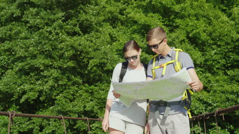 A-Man-And-A-Woman-Are-Studying-The-Map-They-Stand-On-The-Bridge-In-The-Background-Of-A-Picturesque-S