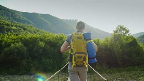 A-Traveler-With-A-Backpack-Walks-Along-A-Wobbly-Bridge-Over-A-Mountain-River-Back-View-4K-Video