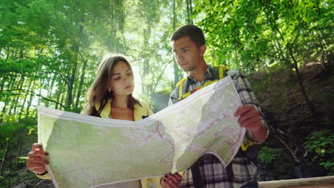 A-Young-Couple-Of-Tourists-Looking-At-A-Map-They-Stand-In-The-Rays-Of-The-Sun-In-The-Forest-Near-The