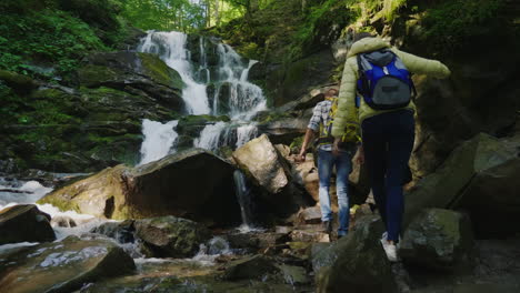 A-Pair-Of-Travelers-With-Backpacks-Climbing-Over-Rocks-To-A-Beautiful-Waterfall-4K-10-Bit-Video