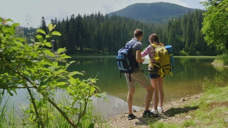 Man-And-Woman-Travelers-Together-They-Orient-Themselves-On-The-Map-The-Man-Looks-Through-Binoculars-