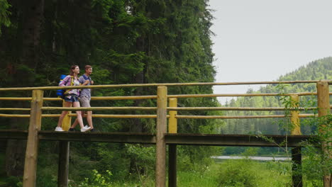 A-Couple-Of-Tourists-Walk-With-Caution-Over-A-Bridge-Over-A-Mountain-River-4K-Video