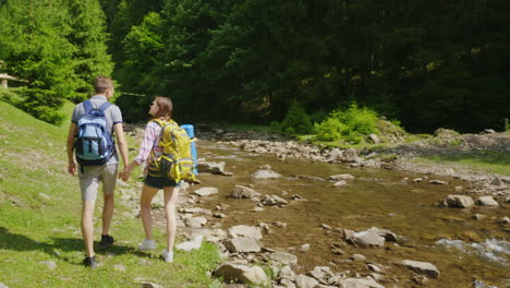 A-Young-Couple-Of-Tourists-Walking-Along-A-Mountain-River-Against-A-Background-Of-Green-Forest-Trave
