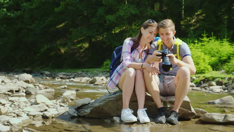 Young-Tourists-Look-At-The-Captured-Photos-On-The-Camera-They-Sit-On-A-Rock-Near-A-Mountain-River-An