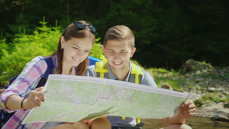 A-Young-Couple-Of-Tourists-Are-Studying-Together-A-Map-They-Sit-In-A-Picturesque-Place-Near-A-Mounta