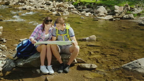 A-Young-Couple-Is-Sitting-On-A-Rock-Near-A-Mountain-River-They-Look-At-The-Map-Together-Planning-The