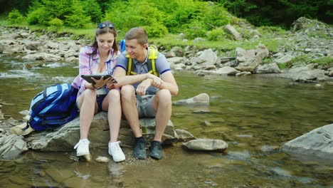 A-Young-Couple-Of-Tourists-Enjoy-A-Tablet-On-A-Trip-Sit-On-A-Rock-Near-A-Mountain-River-4K-Video