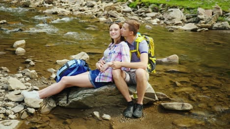 A-Loving-Couple-Of-Tourists-With-Backpacks-Rests-In-A-Picturesque-Place-Near-A-Mountain-River-They-E