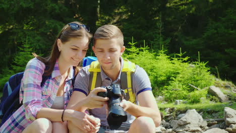 A-Happy-Couple-Of-Tourists-Look-Through-The-Captured-Photos-On-The-Camera-Great-Vacation-And-Good-Me