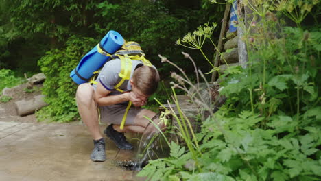 Tired-Traveler-With-A-Backpack-Drinks-Water-From-A-Spring-In-The-Forest-Hd-Video