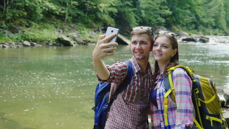 A-Man-With-A-Girlfriend-Are-Photographed-Against-The-Background-Of-A-Mountain-River-On-A-Cloudy-Day-