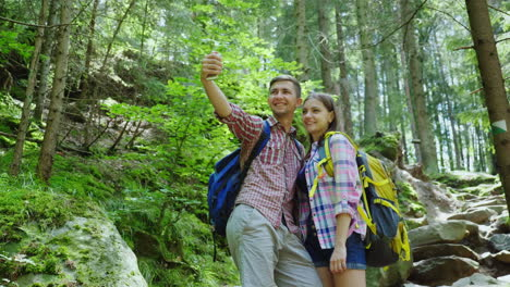An-Attractive-Couple-Of-Tourists-Are-Photographed-In-The-Forest-Selfie-With-Backpacks-On-A-Hike-4K-V